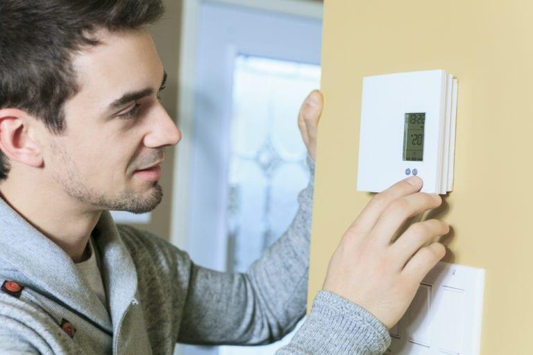 Man touching his thermostat